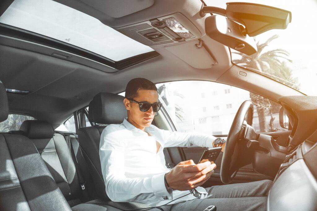 man driving car and holding phone