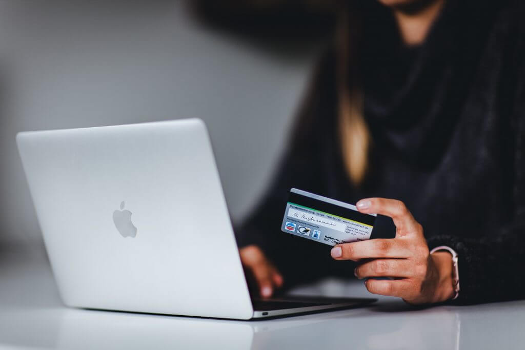 woman holding credit card while at computer