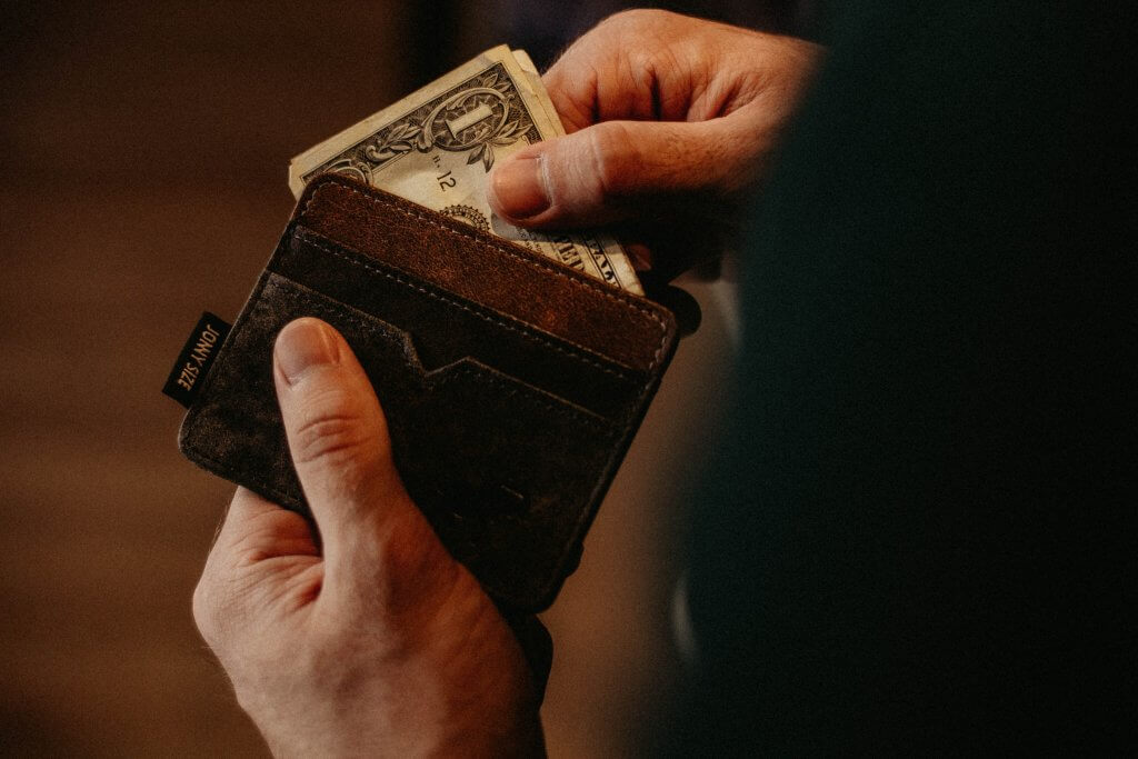 person pulling money out of wallet